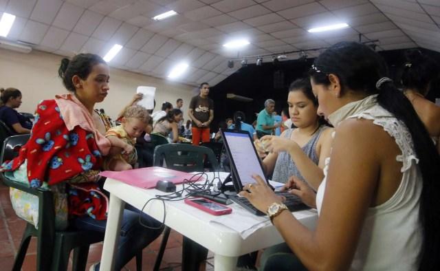 CUC07. CÚCUTA (COLOMBIA), 04/05/2018.- Un grupo de venezolanos recibe asistencia en Cúcuta (Colombia) este 3 de mayo de 2018. Bajo el sol intenso de la ciudad colombiana de Cúcuta, cientos de familias venezolanas que huyeron de su país por la crisis económica y política hacen fila para reclamar los bonos alimentarios que entrega el Programa Mundial de Alimentos (PMA) de la ONU en las zonas de frontera. El proyecto que comenzó este lunes en Cúcuta, capital de Norte de Santander, surge como la primera gran respuesta de la comunidad internacional al delicado estado alimentario del 90 % de los cerca de 35.000 venezolanos que cruzan a diario las fronteras con Colombia en busca de oportunidades. EFE/SCHNEYDER MENDOZA