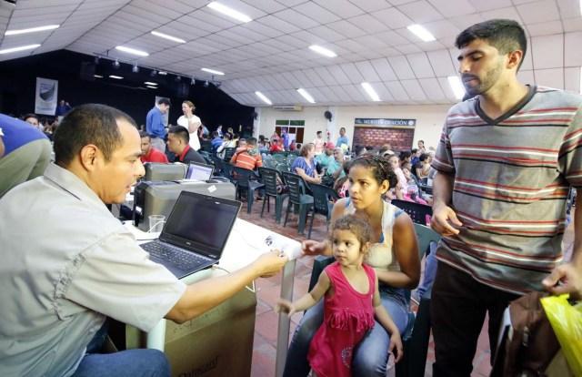 CUC05. CÚCUTA (COLOMBIA), 04/05/2018.- Un grupo de venezolanos recibe asistencia en Cúcuta (Colombia) este 3 de mayo de 2018. Bajo el sol intenso de la ciudad colombiana de Cúcuta, cientos de familias venezolanas que huyeron de su país por la crisis económica y política hacen fila para reclamar los bonos alimentarios que entrega el Programa Mundial de Alimentos (PMA) de la ONU en las zonas de frontera. El proyecto que comenzó este lunes en Cúcuta, capital de Norte de Santander, surge como la primera gran respuesta de la comunidad internacional al delicado estado alimentario del 90 % de los cerca de 35.000 venezolanos que cruzan a diario las fronteras con Colombia en busca de oportunidades. EFE/SCHNEYDER MENDOZA