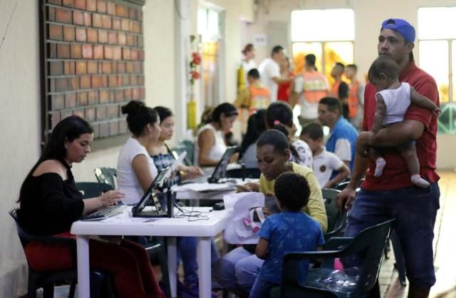 CUC04. CÚCUTA (COLOMBIA), 04/05/2018.- Un grupo de venezolanos recibe asistencia en Cúcuta (Colombia) este 3 de mayo de 2018. Bajo el sol intenso de la ciudad colombiana de Cúcuta, cientos de familias venezolanas que huyeron de su país por la crisis económica y política hacen fila para reclamar los bonos alimentarios que entrega el Programa Mundial de Alimentos (PMA) de la ONU en las zonas de frontera. El proyecto que comenzó este lunes en Cúcuta, capital de Norte de Santander, surge como la primera gran respuesta de la comunidad internacional al delicado estado alimentario del 90 % de los cerca de 35.000 venezolanos que cruzan a diario las fronteras con Colombia en busca de oportunidades. EFE/SCHNEYDER MENDOZA