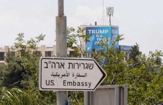 """ATS03. JERUSALÉN (ISRAEL), 14/05/2018.- Un cartel en el que se lee """"Trump es amigo de Sion"""", colocado detrás de una señal indica la dirección hacia la Embajada de Estados Unidos, con motivo de su inauguración en Jerusalén, Israel, hoy, 14 de mayo de 2018. La Policía israelí ha desplegado a miles de agentes en Jerusalén para garantizar la seguridad por el polémico traslado hoy de la Embajada de EEUU desde Tel Aviv a la Ciudad Santa, lo que supone un reconocimiento de facto de la capitalidad israelí de la ciudad, en contra del consenso internacional imperante hasta ahora. EFE/ Atef Safadi"""