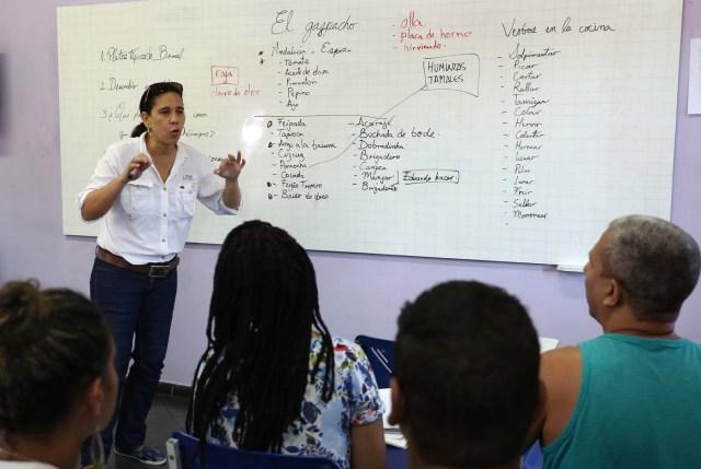 """ACOMPAÑA CRÓNICA: BRASIL VENEZUELA. BRA01. RÍO DE JANEIRO (BRASIL), 18/05/2018.- Fotografía fechada el 16 de mayo de 2018 que muestra a Norma Carrillo mientras enseña español a moradores de la Maré, el complejo de favelas más grande de Río de Janeiro (Brasil). La crisis de Venezuela obligó a Norma Carrillo a abandonar su país para """"empezar de nuevo y rehacer su historia"""" en Brasil donde, mientras busca un empleo que le ayude a establecerse, enseña español a moradores de la Maré, el complejo de favelas más grande de Río de Janeiro. EFE/Marcelo Sayão"""