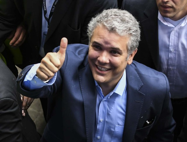 Colombian presidential candidate Ivan Duque, for the Democratic Centre party, gives his thumb up to supporters aftre voting at a polling station in Bogota during the first round of the presidential election in Colombia on May 27, 2018. Voters went to the polls Sunday to choose a new president of Colombia in a divisive election that is likely to weigh heavily on the future of the government's fragile peace deal with the former rebel movement FARC. / AFP PHOTO / Luis ACOSTA