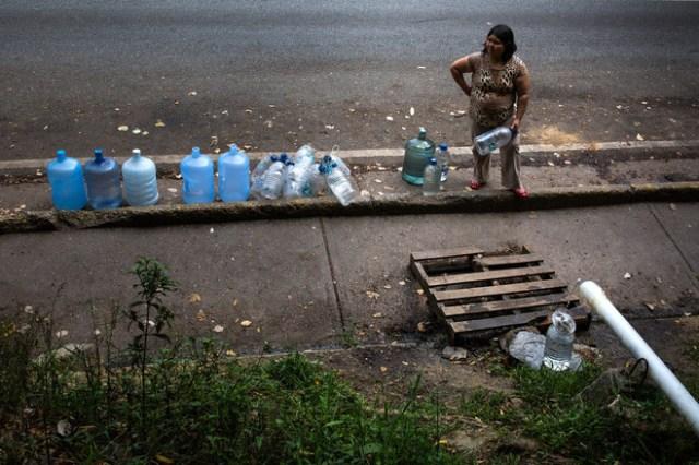 Una mujer llena botellas con el agua que gotea de un chorro resorte al lado de la Cota Mil en Caracas. FOTO: WIL RIERA PARA THE WALL STREET JOURNAL
