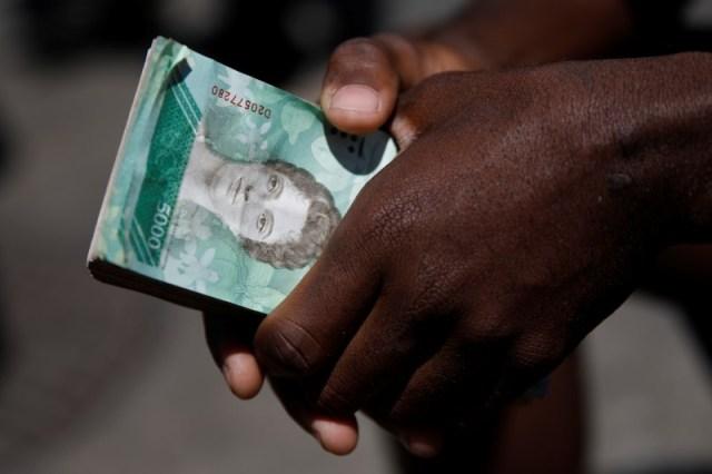 Un vendedor callejero sostiene un fajo de billetes de bolívares mientras espera a clientes en Caracas. Imagen de archivo. 23 de marzo de 2018. REUTERS/Carlos Garcia Rawlins