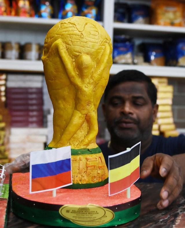 Un trabajador de una confitería organiza la exhibición del modelo de trofeo de la Copa Mundial de la FIFA antes de la próxima Copa Mundial FIFA Rusia 2018, en Calcuta, el 13 de junio de 2018. / AFP PHOTO / Dibyangshu SARKAR