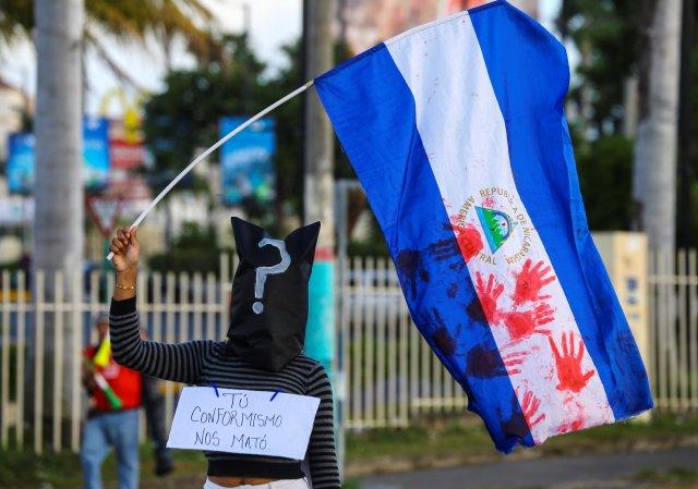 Un manifestante enmascarado sostiene una bandera nacional en apoyo de los adolescentes que murieron en recientes protestas contra el gobierno del presidente de Nicaragua, Daniel Ortega, en Managua, Nicaragua, el 1 de junio de 2018. REUTERS / Oswaldo Rivas