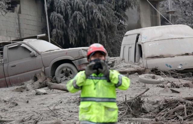 Los vehículos dañados por una erupción del volcán Fuego se ven al lado de un bombero en la comunidad de San Miguel Los Lotes en Escuintla, Guatemala el 4 de junio de 2018. REUTERS / Luis Echeverría