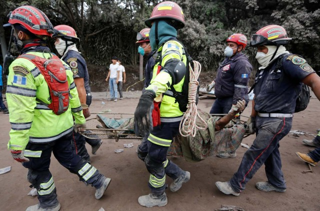 EDITORES DE ATENCIÓN - COBERTURA VISUAL DE ESCENAS DE LESIÓN O MUERTE Los bomberos portan un cuerpo en un área afectada por la erupción del volcán Fuego en la comunidad de San Miguel Los Lotes en Escuintla, Guatemala 4 de junio de 2018. REUTERS / Luis Echeverria PLANTILLA FUERA