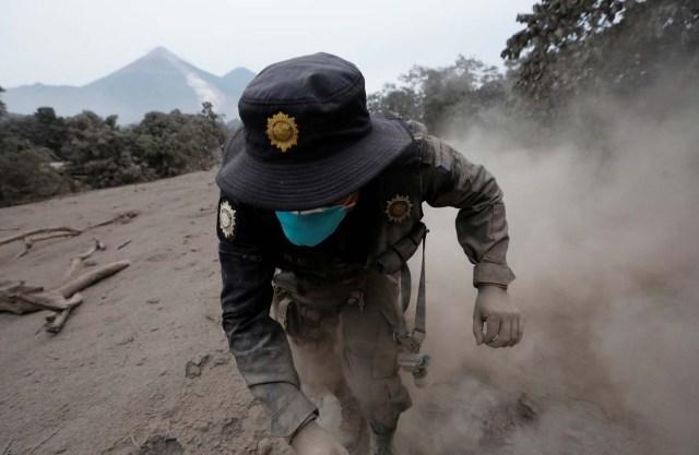 Un oficial de policía tropieza mientras huye después de que el volcán Fuego arrojara un nuevo flujo piroclástico en la comunidad de San Miguel Los Lotes en Escuintla, Guatemala, el 4 de junio de 2018. REUTERS / Luis Echeverría