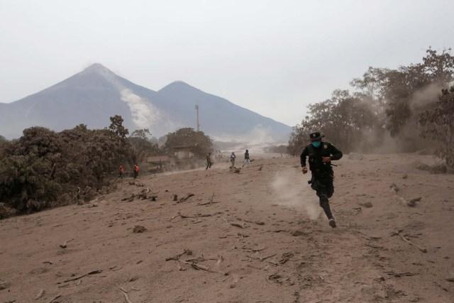 Un oficial de policía huye luego de que el volcán Fuego arrojara un nuevo flujo piroclástico en la comunidad de San Miguel Los Lotes en Escuintla, Guatemala, el 4 de junio de 2018. REUTERS / Luis Echeverría