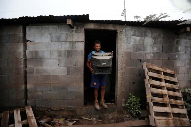 Un residente recupera un televisor de su casa en un área afectada por la erupción del volcán Fuego en la comunidad de San Miguel Los Lotes en Escuintla, Guatemala, el 4 de junio de 2018. REUTERS / Luis Echeverría