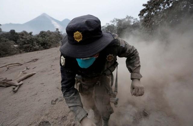 Un oficial de policía tropieza mientras huye después de que el volcán Fuego arrojara un nuevo flujo piroclástico en la comunidad de San Miguel Los Lotes en Escuintla, Guatemala, el 4 de junio de 2018. REUTERS / Luis Echeverria TPX IMÁGENES DEL DÍA