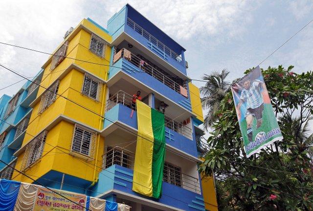 Los fanáticos cuelgan una gran bandera de un edificio residencial junto a un cartel con el futbolista argentino Lionel Messi antes de la Copa Mundial de la FIFA, en Calcuta, India, el 10 de junio de 2018. REUTERS / Rupak De Chowdhuri