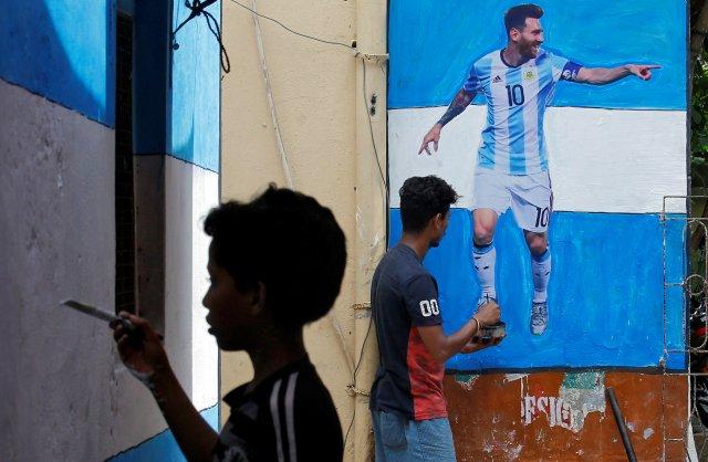 Un niño pinta una pared con los colores de la bandera de Argentina junto a un hombre dando los toques finales a un jugador de fútbol Lionel Messi después de pegarlo en una pared en un callejón antes de la Copa Mundial de la FIFA, en Calcuta Un niño pinta una pared con los colores de la bandera de Argentina junto a un hombre dando los toques finales a un jugador de fútbol Lionel Messi después de pegarlo en una pared en un callejón antes de la Copa Mundial de la FIFA, en Calcuta, India, junio 10, 2018. REUTERS / Rupak De Chowdhuri