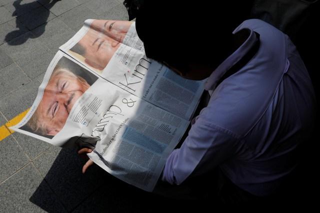 Un periodista lee un periódico local que muestra un artículo sobre la cumbre entre el presidente estadounidense Donald Trump y el líder norcoreano Kim Jong Un cerca del hotel St. Regis en Singapur el 11 de junio de 2018. REUTERS / Tyrone Siu