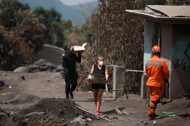 Un policía ayuda a un residente a llevar las pertenencias recuperadas de su casa en un área afectada por la erupción del volcán Fuego en San Miguel Los Lotes en Escuintla, Guatemala, el 11 de junio de 2018. REUTERS / Jose Cabezas