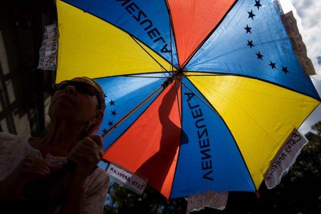 Una persona abre una sombrilla con los colores de la bandera venezolana durante una de las manifestaciones en contra de las elecciones presidenciales hoy, sábado 17 de marzo de 2018, en Caracas (Venezuela) EFE/Miguel Gutiérrez
