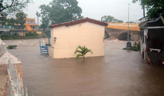 Fotografía cedida por la Agencia Cubana de Noticias (ACN), de una calle totalmente inundada este 28 de mayo de 2018, en Sancti Spíritus (Cuba). La región central de Cuba ha quedado incomunicada debido a las intensas lluvias de los últimos días que han provocado inundaciones y la crecida de ríos en las provincias de Villa Clara, Sancti Spíritus y Cienfuegos donde fueron evacuadas más de 15.000 personas, informaron medios oficiales. EFE/ACN/Oscar Alfonso