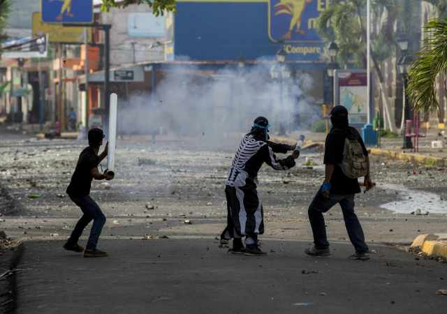 -FOTODELDIA- NI6033. MASAYA (NICARAGUA), 02/06/2018.- Tres jóvenes lanzan un mortero en un enfrentamiento con la Policía Nacional en la ciudad de Masaya (Nicaragua) hoy, sábado 02 de junio de 2018, durante el día número 46 de protestas en contra del gobierno de Daniel Ortega. La Policía de Nicaragua reportó hoy dos muertos, dos heridos y 11 detenidos en el marco de las protestas contra el Gobierno de Daniel Ortega. EFE/Jorge Torres