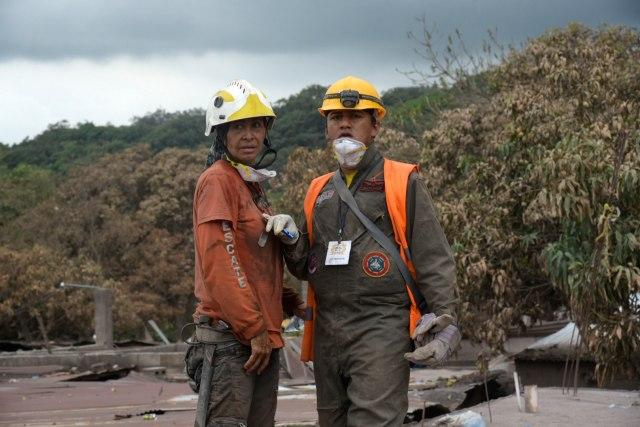 GUO119. EL RODEO (GUATEMALA), 10/06/2018.- Fotografía de dos rescatistas durante la búsqueda de víctimas de la erupción del volcán de Fuego hoy, domingo 10 de junio de 2018, en la población de El Roedo (Guatemala). La violenta erupción del volcán de Fuego, el domingo pasado, que deja ya 110 muertos, mantiene en alerta máxima a Guatemala porque el coloso se resiste a volver a la calma, y las brigadas de rescate reanudaron hoy la búsqueda de más víctimas. El coloso, situado a 50 kilómetros al oeste de la capital, entre los límites de los departamentos de Chimaltenango, Sacatepéquez y Escuintla, amaneció este domingo con hasta nueve explosiones por hora. EFE/ Rodrigo Pardo