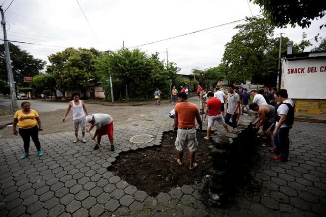"""Manifestantes arman una barricada hoy, 11 de junio de 2018, durante enfrentamientos con la Policia Nacional en los barrios de Managua (Nicaragua). Este lunes por la mañana la Policía Nacional y grupos """"parapoliciales"""" atacaron los llamados """"barrios orientales"""" de Managua con armas de guerra, en respuesta a múltiples barricadas que edificó la población en las calles para impedir el paso de fuerzas de choque oficialistas. EFE/Bienvenido Velasco"""