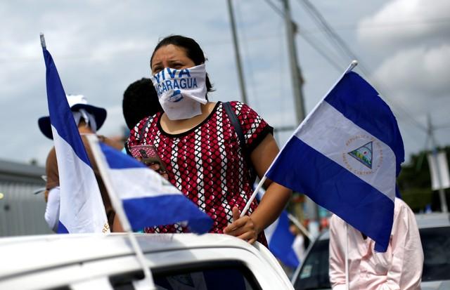 Una manifestante lleva banderas nacionales durante una protesta en Managua contra el Gobierno del presidente Daniel Ortega, Nicaragua, 10 de junio de 2018. REUTERS/Jorge Cabrera - RC185EA14230