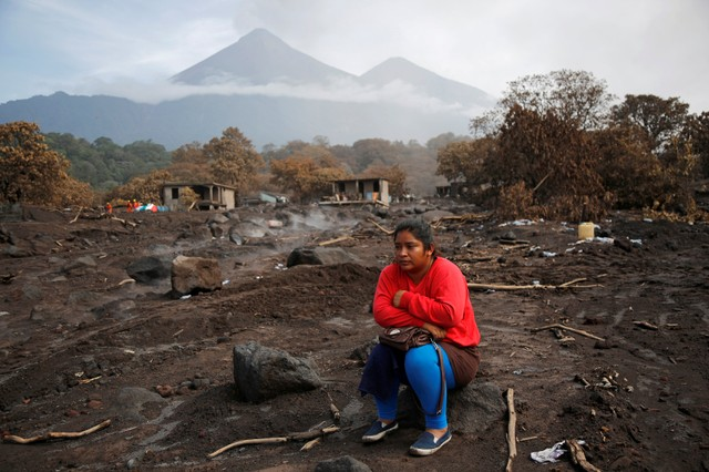 Milvia Vasquez observes an excavator removing ash from the site where she presumes her brothers are buried in an area affected from the eruption of Fuego volcano in San Miguel Los Lotes, in Escuintla, Guatemala June 13, 2018. REUTERS/Luis Echeverria     TPX IMAGES OF THE DAY