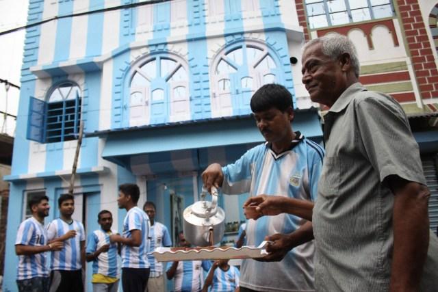 Shib Shankar Patra (2R), aficionado al fútbol del equipo argentino, sirve té a los fanáticos y clientes en frente de su departamento pintado en azul y blanco, antes de la próxima Copa Mundial 2018, el 11 de junio de 2018. Un juego duro El aficionado argentino en India ha pintado su casa con los colores azul y blanco del equipo antes de la Copa del Mundo, diciendo que su amor por los hombres de Lionel Messi no tiene límites. La pasión del residente de Kolkata Shib Shankar Patra por Argentina comenzó durante el Mundial de 1986 cuando Diego Maradona ayudó al equipo a ganar el codiciado trofeo. AFP