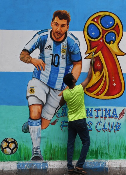 Un fanático del fútbol indio pinta una foto del futbolista argentino Lionel Messi en una carretera, antes de la próxima Copa Mundial FIFA 2018, en Calcuta el 10 de junio de 2018. Dibyangshu SARKAR / AFP