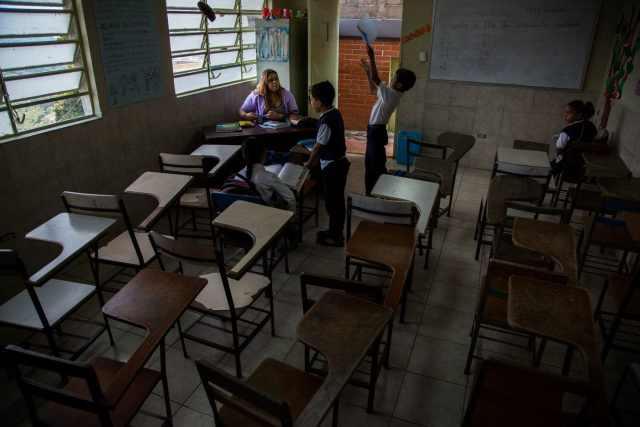 Kory Hernández, de 24 años, atiende a estudiantes mientras sustituye a un maestro desaparecido en un suburbio del sur de Caracas. Los hijos de Hernández estudian en la misma escuela, Aquiles Nazoa Elementary. (Wil Riera / For The Washington Post)