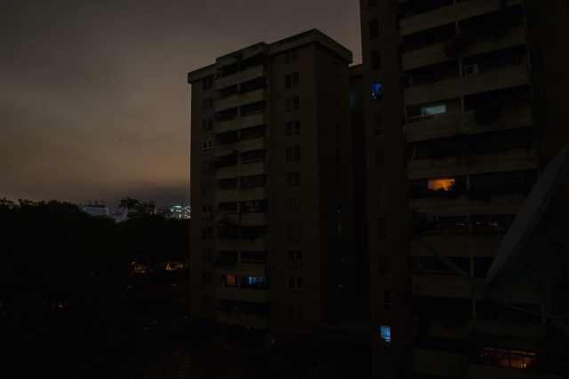 Una vista de un complejo residencial donde la gente usa luz de teléfonos celulares o velas durante un apagón parcial en el barrio La Carlota de Caracas el 14 de mayo. (Wil Riera / For The Washington Post)