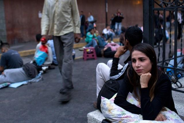 Antonieta Suárez se sienta después de pasar la noche esperando en línea por un nuevo pasaporte. Fotógrafo: Manaure Quintero / Bloomberg