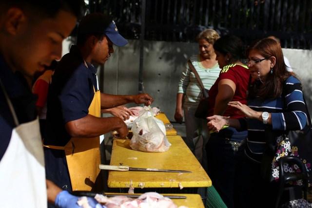 Un vendedor vende carne de pollo en un puesto de carnicería en un mercado callejero en Caracas, Venezuela, 10 de noviembre de 2018. REUTERS / Manaure Quintero
