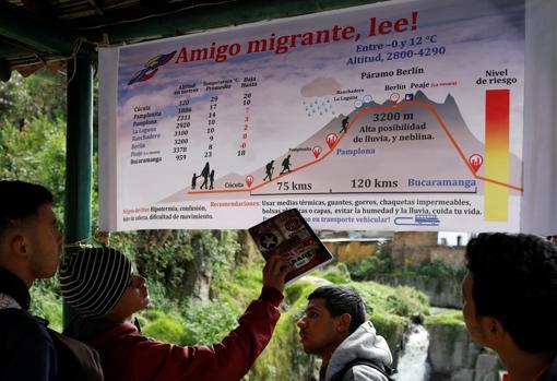 Venezolanos miran una pancarta con información sobre la ruta de Cúcuta a Bucaramanga – Reuters
