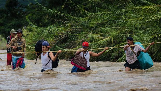 Venezolanos cruzan ilegalmente la frontera con Colombia. Julio Quintero, el primero a la derecha, murió al ser arrastrado por la fuerza del agua – Isaac Paniza