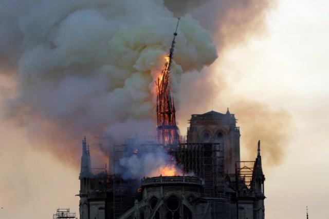 El campanario de la histórica catedral de Notre-Dame se derrumba cuando la catedral se ve envuelta en llamas en el centro de París el 15 de abril de 2019. - Un enorme incendio azotó el techo de la famosa Catedral de Notre-Dame en el centro de París el 15 de abril de 2019. enviando llamas y enormes nubes de humo gris ondeando en el cielo. Las llamas y el humo se desplomaron en la torre y el techo de la catedral gótica, visitada por millones de personas al año. Un portavoz de la catedral dijo a la AFP que la estructura de madera que sostenía el techo estaba siendo destruida por el incendio. (Foto por Geoffroy VAN DER HASSELT / AFP)