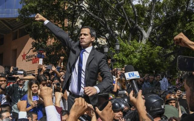 O presidente interino do líder da oposição venezuelana, Juan Guaido, cumprimenta quando se dirige à Assembléia Nacional, em Caracas, em 7 de janeiro de 2020. (Foto por Yuri CORTEZ / AFP)