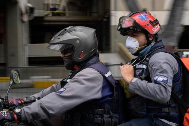 """Miembros del grupo paramédico de la ONG """"Ángeles de las vias"""" viajan en una motocicleta en Caracas, el 10 de junio de 2020, en medio de la nueva pandemia de coronavirus de COVID-19"""