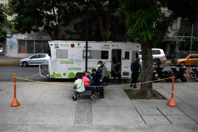 """Miembros del grupo paramédico de la ONG """"Ángeles de las vias"""" ayudan a una persona en su sede, una autocaravana, en el barrio de Los Palos Grandes, en Caracas, el 10 de junio de 2020, en medio de la nueva pandemia de coronavirus COVID-19."""
